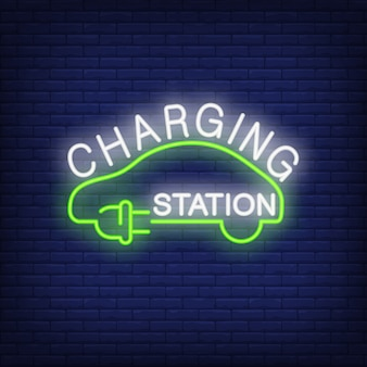 Charging station neon sign. green plug and cord in shape of car on brick wall.