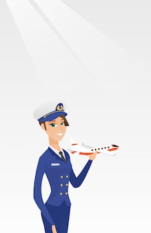 Cheerful airline pilot with the model of airplane.