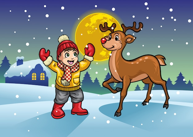 Cheerful boy with the reindeer in the middle of snowy winter