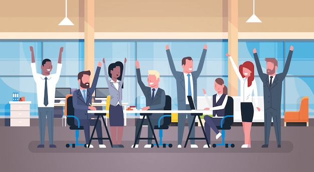 Cheerful business team sitting together at desk happy group of successful businesspeople with raised