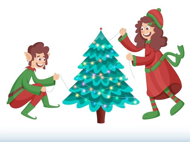陽気なエルフと女の子は白い背景の上のガーランドの照明からクリスマスツリーを飾った