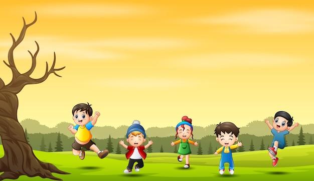 自然の背景でジャンプして笑っている陽気な小さな子供たち