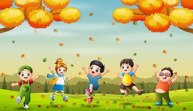 秋の背景にジャンプする陽気な小さな子供たち