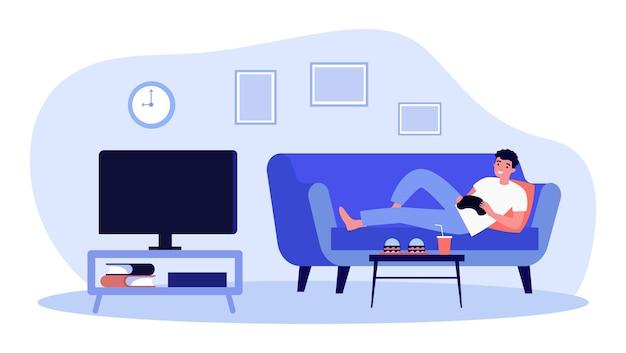 Веселый человек, лежа на диване и играя в видеоигры
