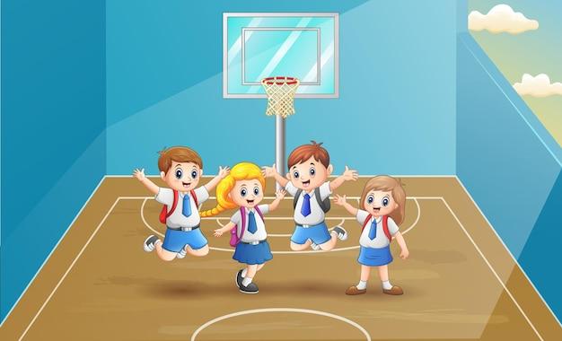 バスケットボールコートでジャンプする陽気な学校の子供たち