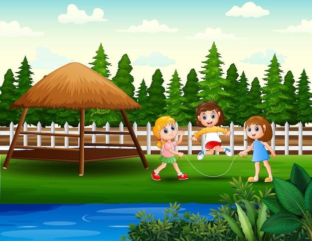 Веселые дети играют в скакалку на заднем дворе