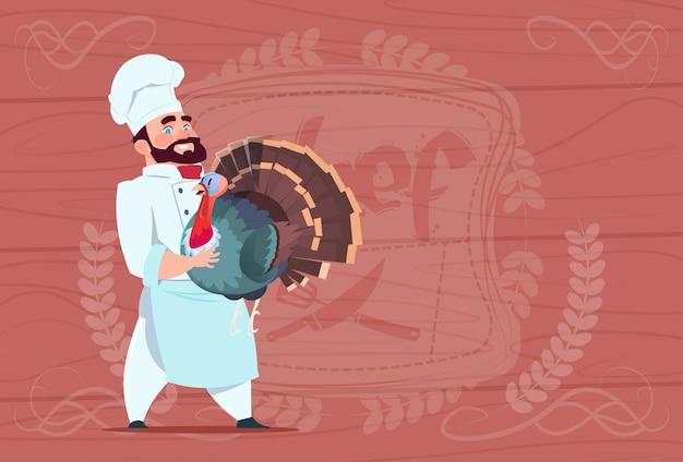 Chef cook hold turkey smiling cartoon restaurant chief in white uniform over wooden textured background