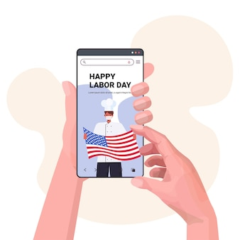 Chef in uniform on smartphone screen holding usa flag happy labor day celebration
