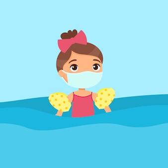 Ребенок с удовольствием в воде с медицинской маской. защита от вирусов, аллергия девушка плавает с надувными рукавами. малыш в купальнике, наслаждаясь летние мероприятия.