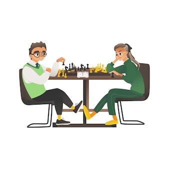 子供、男の子とメガネをかけた女の子が向かい合ってチェスをします。