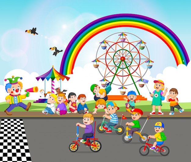 The children are playing near the carnival and riding the bicycle
