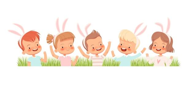 うさぎに身を包んだ子供たちは笑い、草の中で手を振る。子供たちはイースターであなたを祝福します。 。