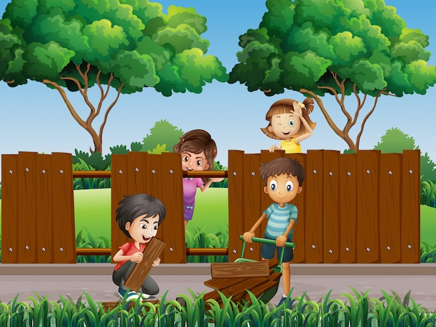 Children fixing fence in the park