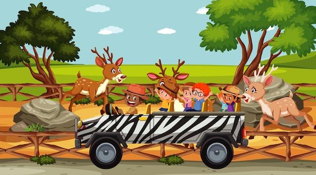 많은 사슴이 있는 동물원의 어린이 그룹