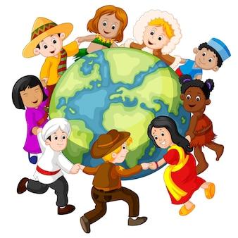 Children holding hands around the world Premium Vector