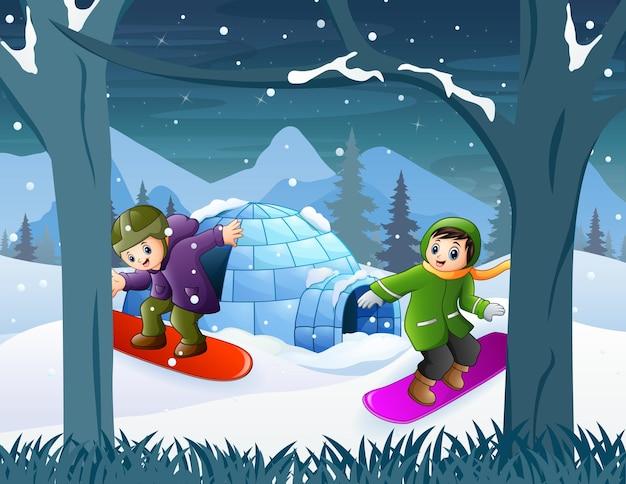 冬の風景の中のスノーボードの子供たち