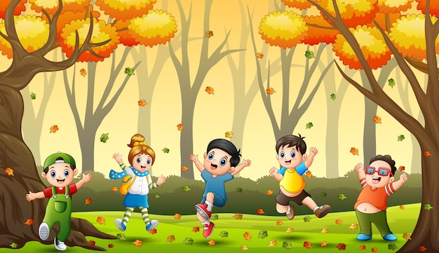 Children playing with fallen leaves in autumn forest