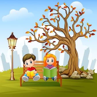 도시 공원 벤치에서 책을 읽는 아이들