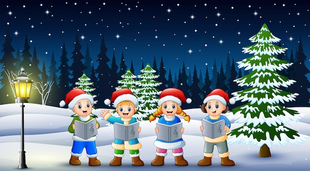 Children singing christmas carols in winter clothes and santa hat with snowy pine