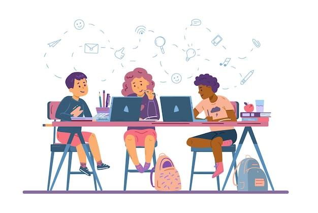 Дети учатся в онлайн-школе, сидя за партой с портативными компьютерами и книгами