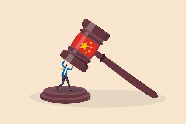 新しいルールの概念で会社を操作または制御する中国政府の規制、ビジネスマンの事業主または投資家は、中国の旗を持つ大きなガベルハンマーから生き残ることを試みます。