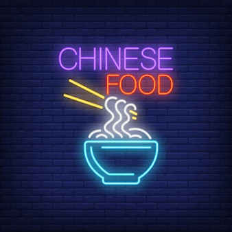 Chinese food neon sign. bowl of noodles with chopsticks on brick wall background.