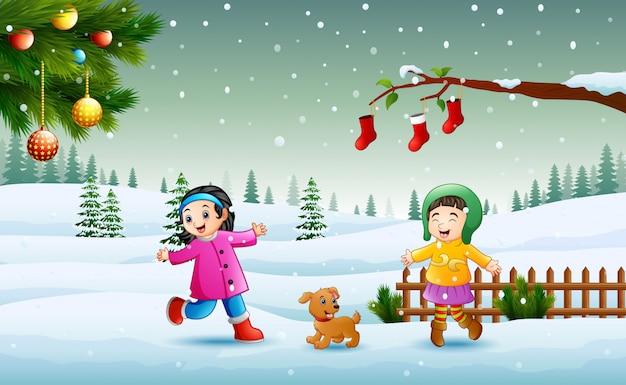 クリスマスの日に雪の上で遊んでいる冬のchlotesを着ている子供たち