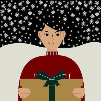 Рождественские и новогодние подарки, давая концепцию. красивая женщина, держащая подарочную коробку с бантом. волосы в снежинках.