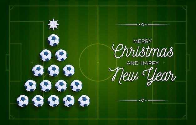 クリスマスと新年のグリーティングカード。クリスマスと新年のお祝いのサッカーフィールドの背景にサッカーサッカーボールによって作られた創造的なクリスマスツリー。スポーツグリーティングカード
