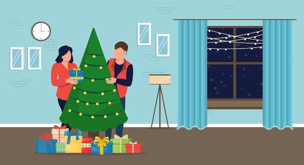 家でのクリスマス。カップルはクリスマスツリーを飾り、プレゼントを入れました。