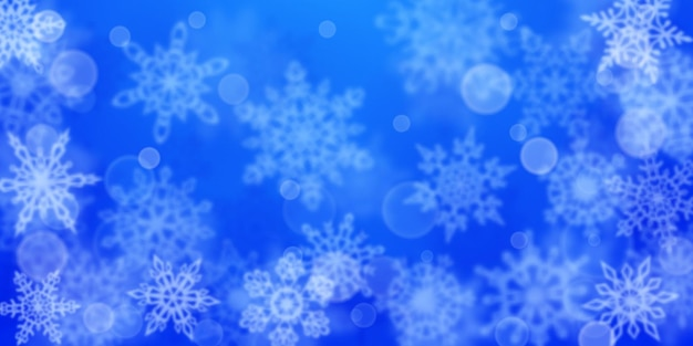 Christmas background of blurry snowflakes in blue colors