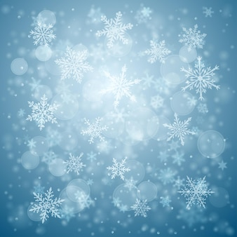Christmas background of complex blurred and clear falling snowflakes in blue colors with bokeh effect