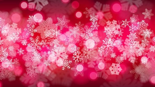 진홍색의 보케 효과가 있는 크고 작은 눈송이의 크리스마스 배경