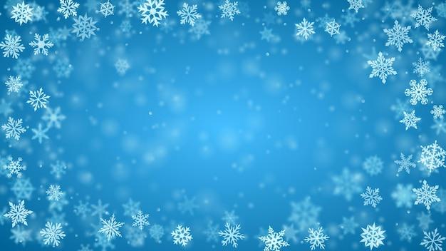 보케 효과가 있는 밝은 파란색 색상의 복잡하고 흐릿하고 맑은 떨어지는 눈송이의 크리스마스 배경