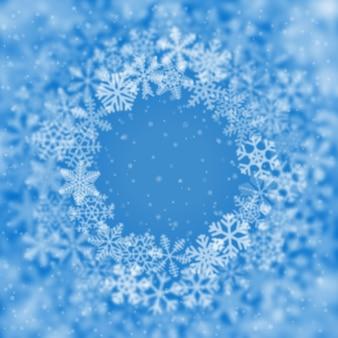 Новогодний фон из снежинок разной формы, размытия и прозрачности, расположенных по кругу, на голубом фоне
