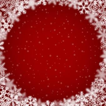 赤い背景の上に、円形に配置された、さまざまな形、ぼかし、透明度の雪片のクリスマスの背景