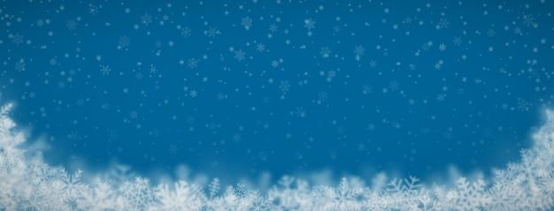 Новогодний фон из снежинок разной формы, размера, размытия и прозрачности на синем фоне