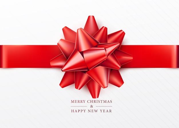 クリスマスの背景。赤いリボンとリボンが付いた白いギフトボックス。上面図。あいさつテキストサイン。メリークリスマスと新年あけましておめでとうございます。