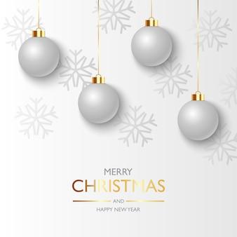 掛かる銀のクリスマスボールと雪のクリスマスの背景