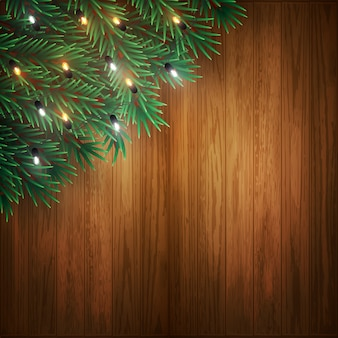 Christmas background with pine tree branches and colorful lights on wood