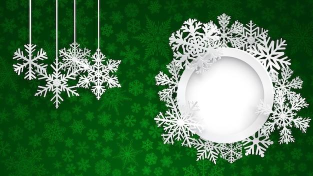 Новогодний фон с круглой рамкой в окружении снежинок и несколько висящих снежинок на зеленом фоне маленьких снежинок. рождественская иллюстрация со снежинками и круглая фоторамка