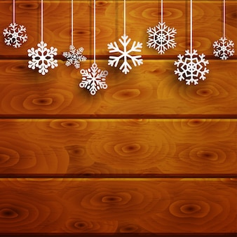 Christmas background with white hanging snowflakes on brown wooden planks