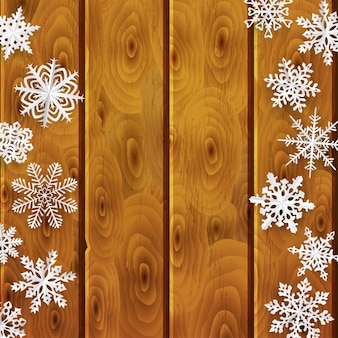 Christmas background with white paper snowflakes on brown wooden planks