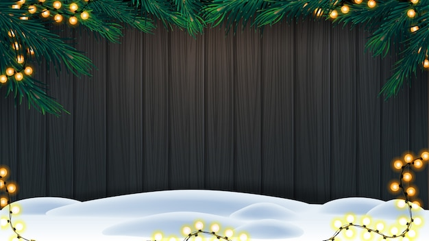 Christmas background, wooden wall with frame of christmas tree branches, garland and snow on floor