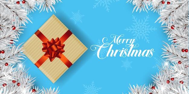 Рождественский дизайн баннера с подарком и ветвями деревьев