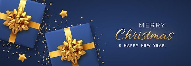 クリスマスバナー。金色の弓、金色の星、キラキラの紙吹雪が付いたリアルな青いギフトボックス。