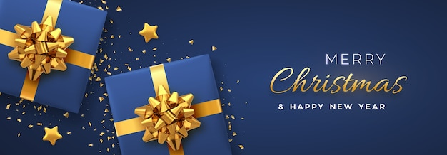 Christmas banner. realistic blue gift boxes with golden bow, gold stars and glitter confetti.