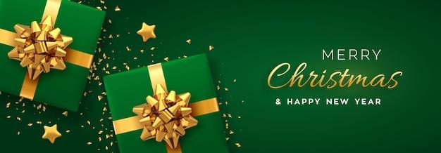 クリスマスバナー。金色の弓、金色の星、キラキラの紙吹雪が付いたリアルな緑色のギフトボックス。クリスマスの背景、ヘッダーのウェブサイト。