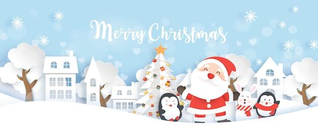 サンタクロースのペンギンと雪の村の紙のカットとクラフトスタイルのウサギのクリスマスバナー。