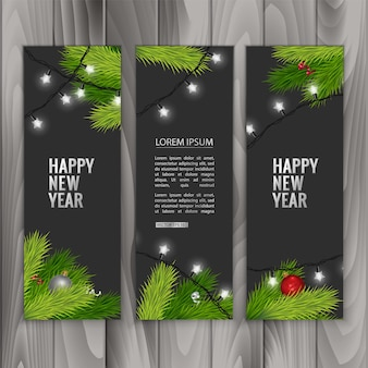 Christmas banners with fir branches decorated with ribbons red balls and garlands on wood background